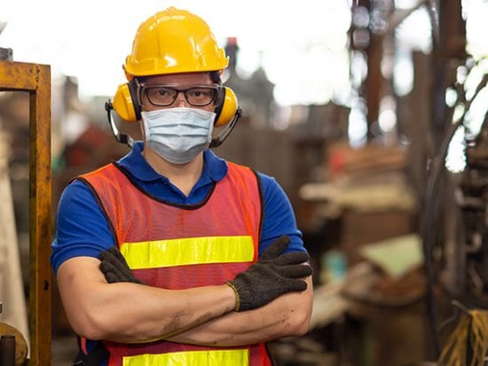 Resuming business: worker wearing face shield or disposable face mask during working service in factory to prevent Coronavirus(Covid-19).